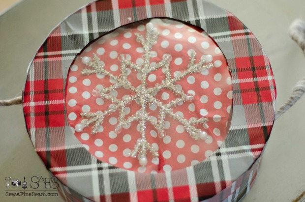 wrapping paper covered gift box upcycle with an ornament under the see-through lid