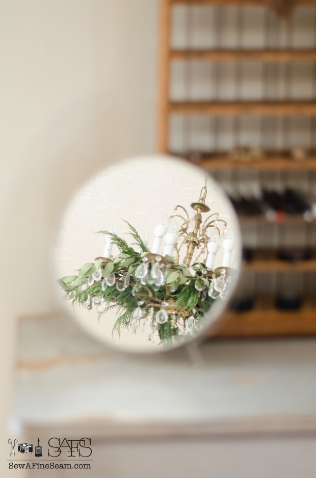 Vintage mirror reflecting a greenery stuffed chandelier