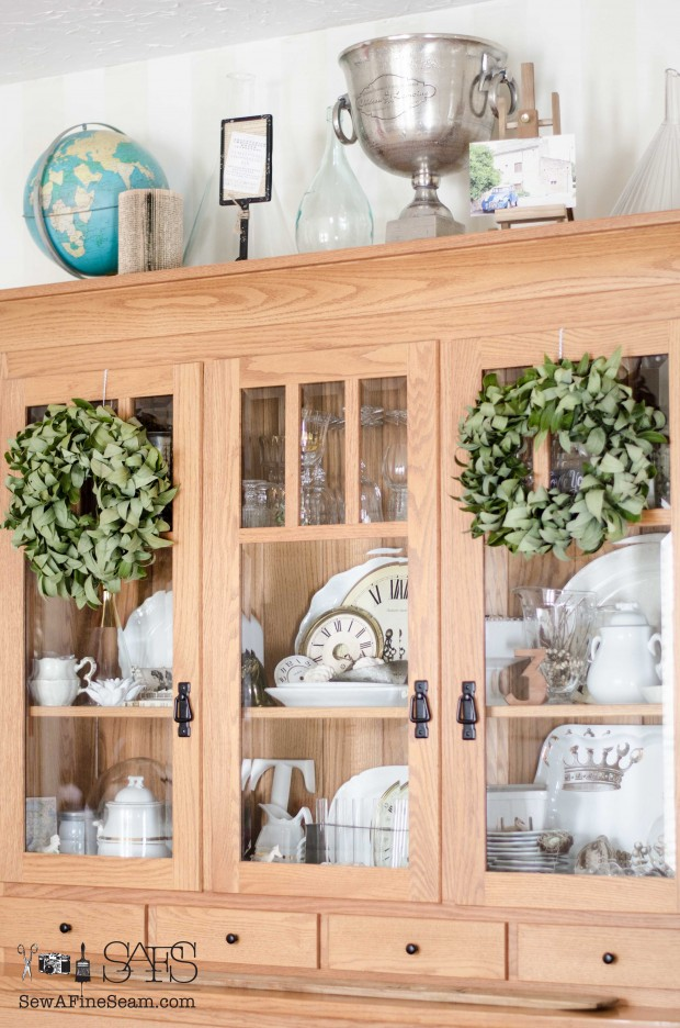 China hutch filled with white ironstone and clock faces and still sporting the bay wreaths