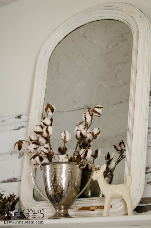 adding farmhouse appeal with cotton floral stems for springtime against a vintage mirror