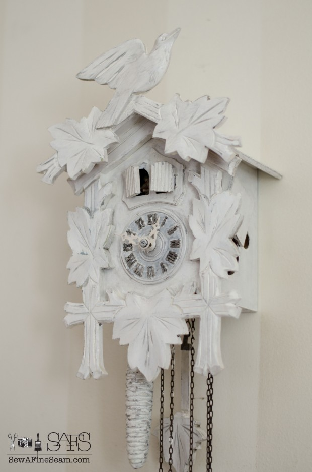 cuckoo clock painted white and hung on a white striped wall