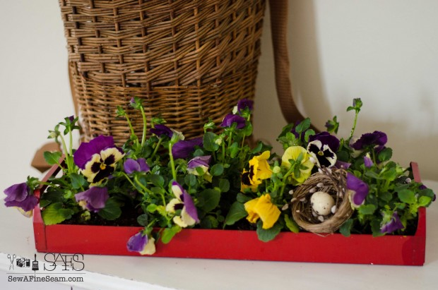spring farmhouse decor toolbox of pansies with a nest tucked in for fun