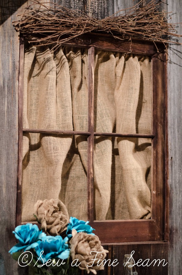 burlap curtain hung behind and old window inside a shop