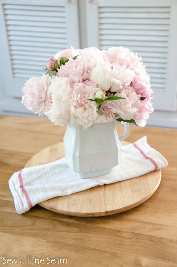 White cupboard creates a lot of storage - peonies create beautiful decor