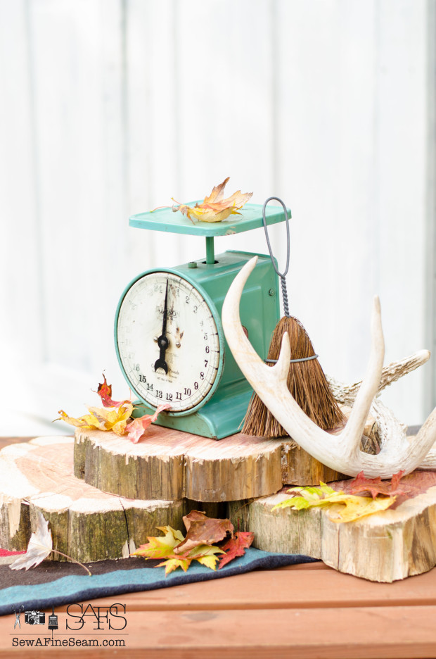 Fall centerpiece using cedar wood slices, leaves, antlers, and a vintage scale