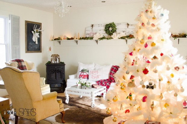 living room decked out for chrismtas with pillows and plaid and greenery