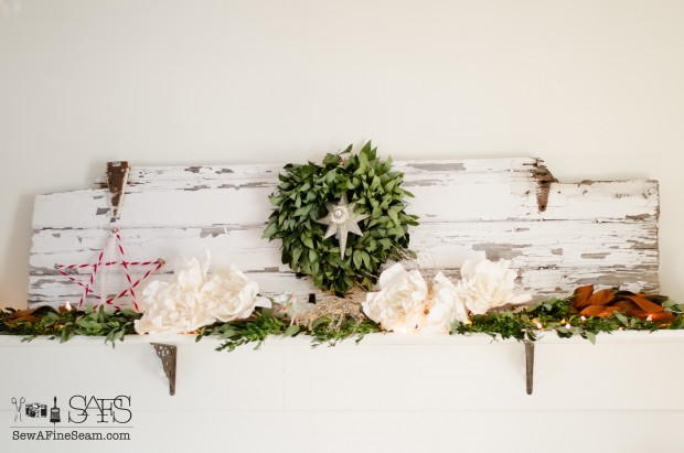 christmas mantel decorated with an old barn door and greenery