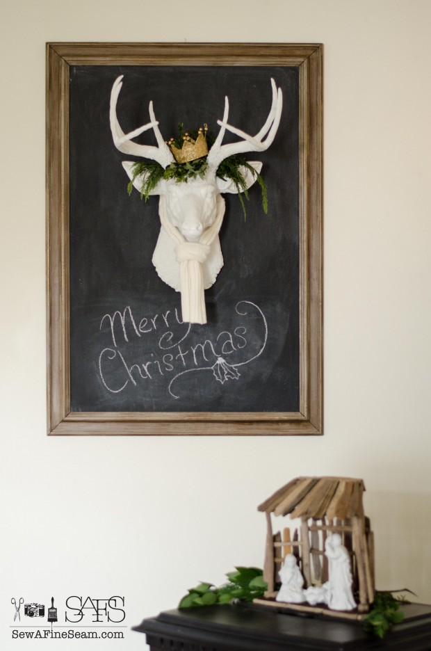 faux deer head with greenery and gold crown on a chalkboard
