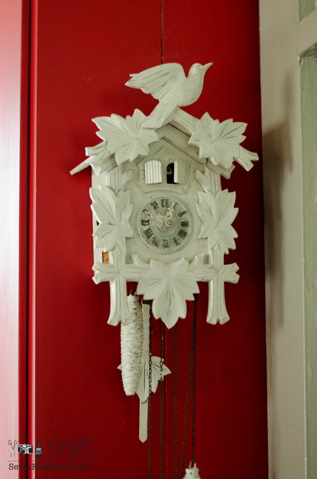 finished cuckoo clock makeover against a red cupboard