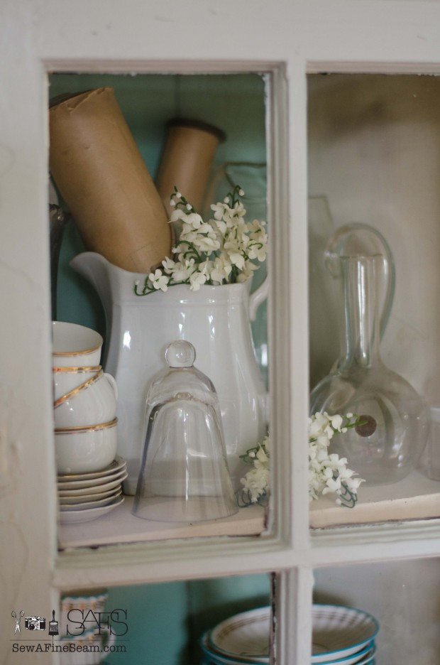 spring farmhouse decor in the corner cupboard
