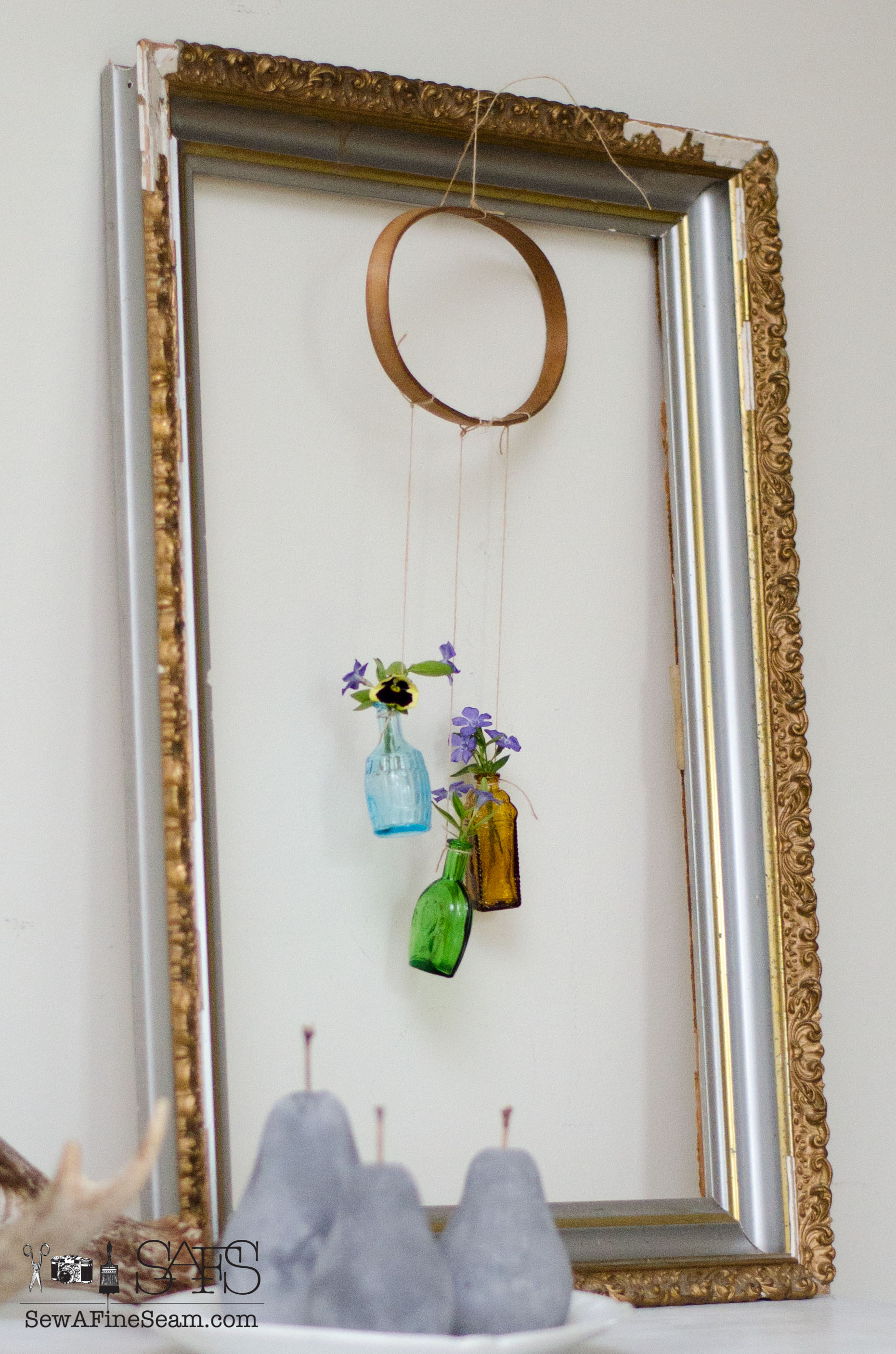 Flower vase made of tiny bottles sew a fine seam flower vases from tiny bottles an old embroidery hoop and a vintage frame for springtime decor reviewsmspy
